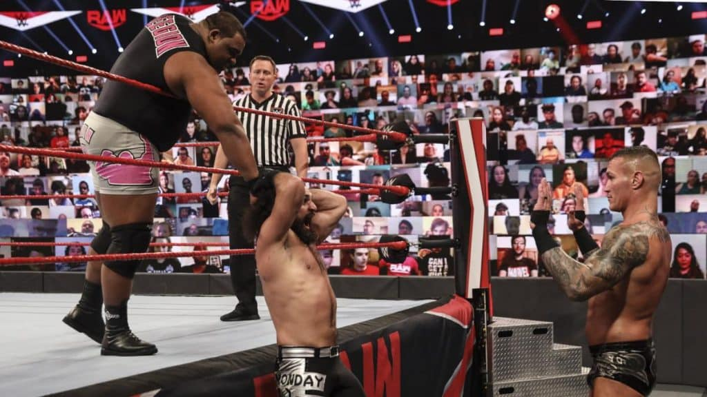 Keith Lee interrupts Rollins and Orton's argument by grabbing Rollins by the hair