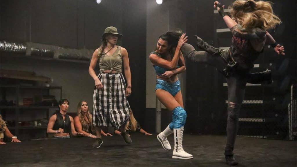 Billie Kay takes a kick from Jessamyn Duke while blocked in by Marina Shafir