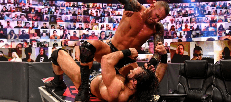 Randy Orton pounds on Drew McIntyre on the announce desk