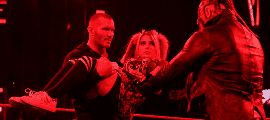 Randy Orton holds Alexa Bliss with The Fiend holding out his arms to take her back