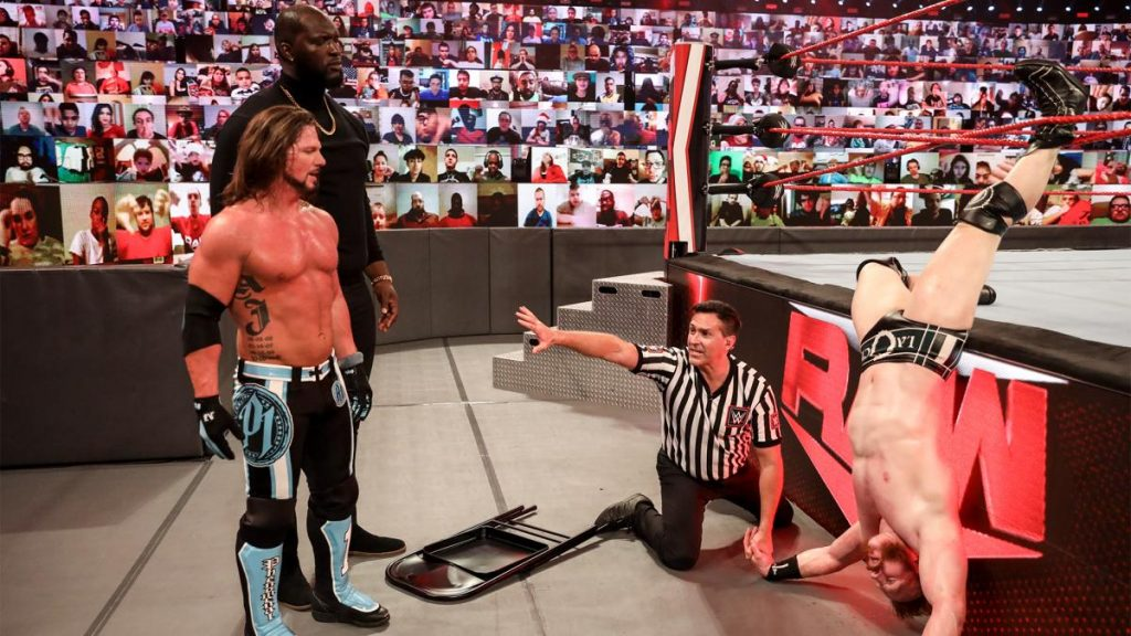 A ref tries to stop AJ Styles attacking a helpless Sheamus