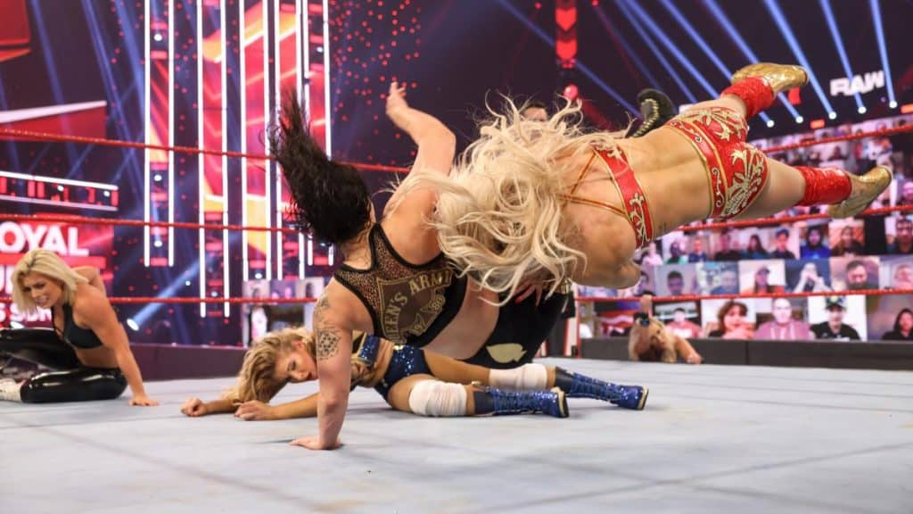 Charlotte Flair spears Shayna Baszler with Dana Brooke and Mandy Rose in the background
