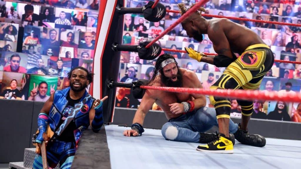 Xavier Woods looks on while Kofi Kingston has Elias in the corner