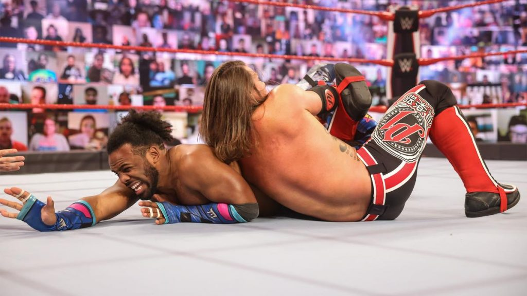 AJ Styles with Xavier Woods in a calf crusher