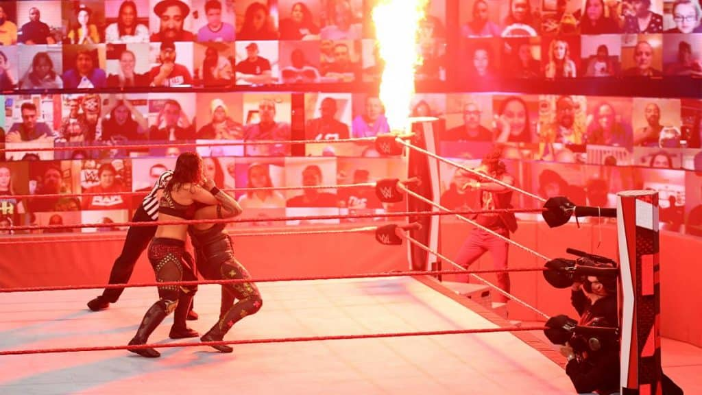 Shayna Baszler with Tamina in a Kirifuda while fire shoots out of the ringpost