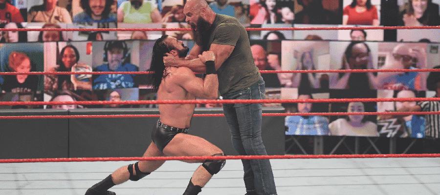 Braun Strowman with Drew McIntyre on his knees