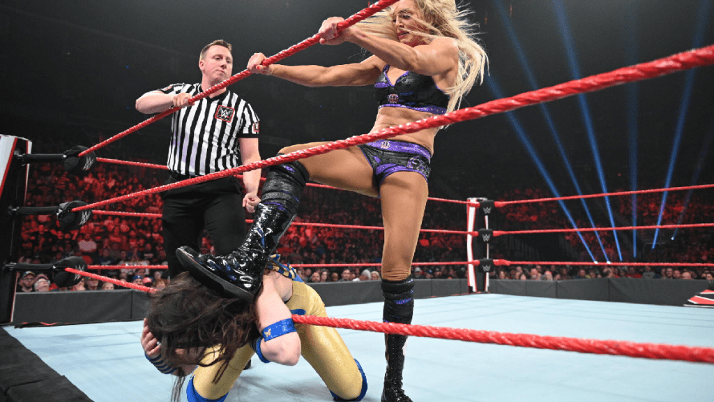 Charlotte Flair steps on Nikki A.S.H.'s neck on the ropes