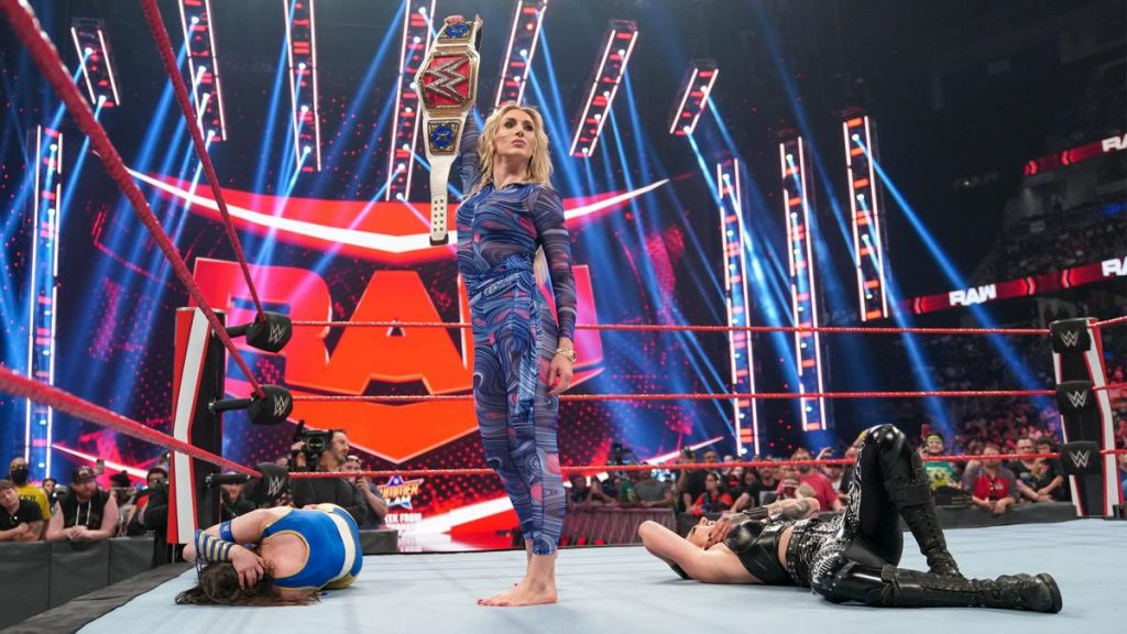 Charlotte Flair stands over Nikki A.S.H. and Rhea Ripley