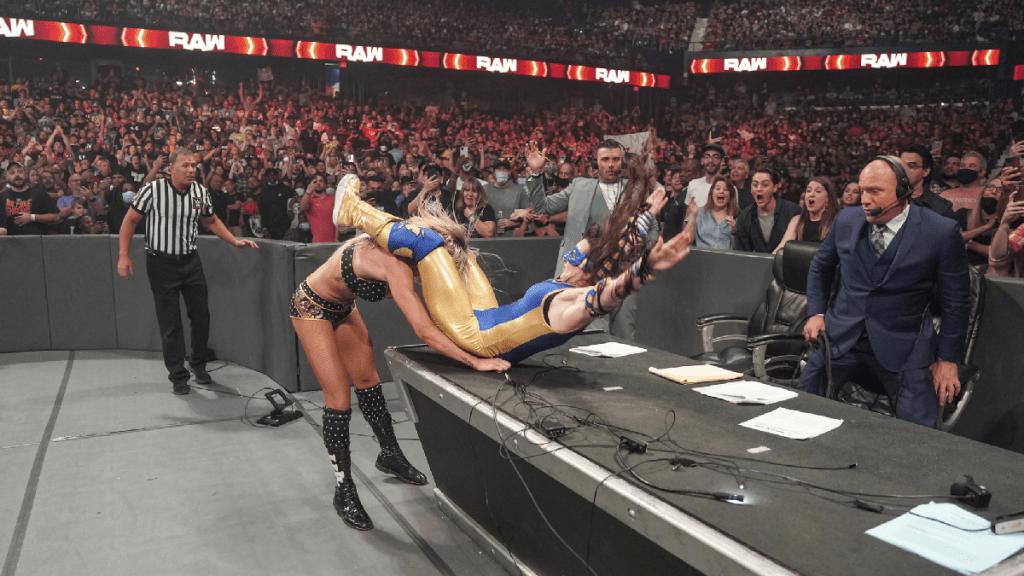 Charlotte Flair puts NIkki A.S.H. through the announce desk