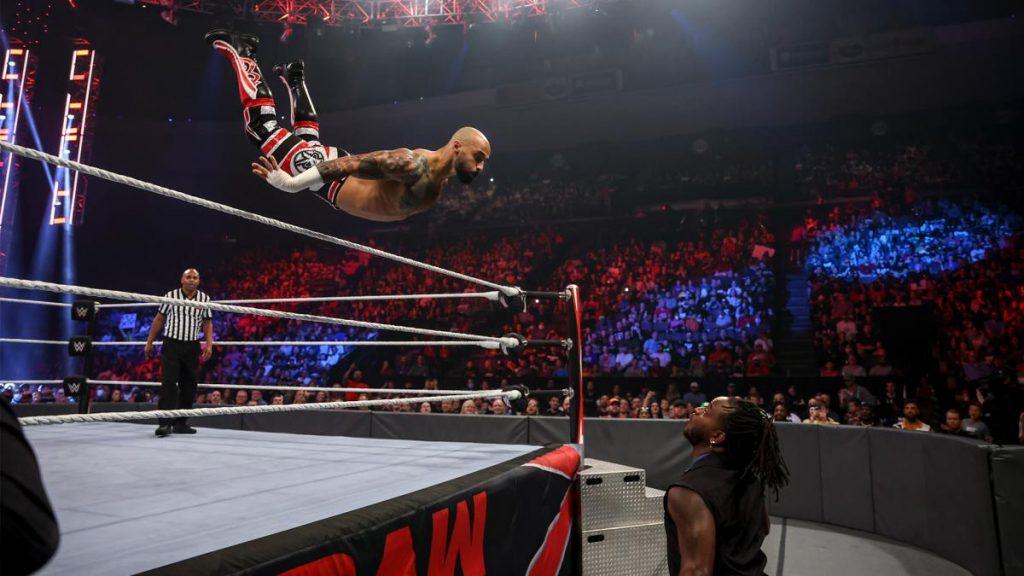 Ricochet flies over the top rope towards Reggie